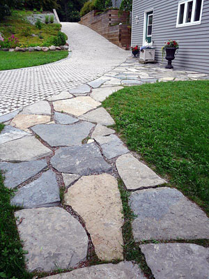 Permeable Turfstone stabilizes an eroding boat launch driveway. The lower limestone deck secures the driveway against runoff erosion.